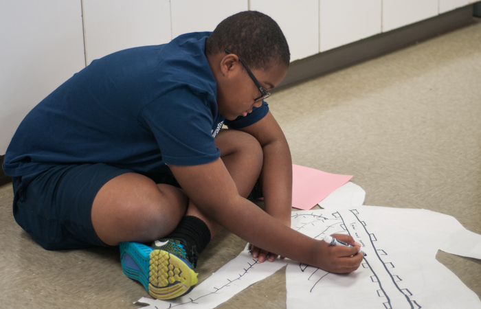 A student works on drawing the nervous system on his life-size anatomical model.