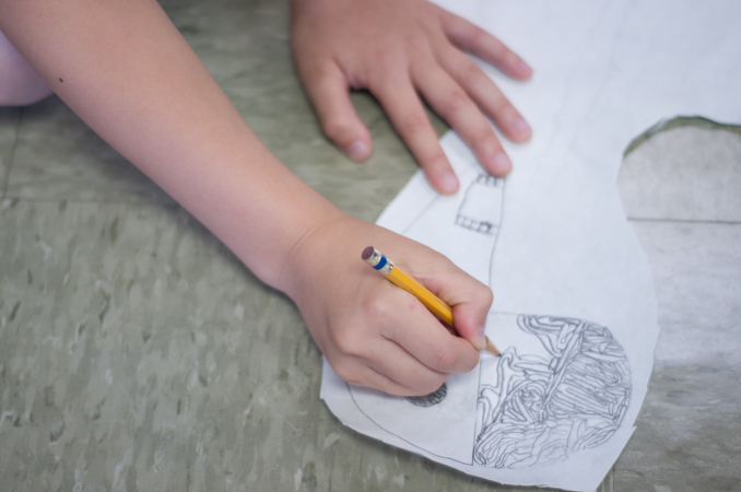 A student meticulously works on a drawing of a human brain.