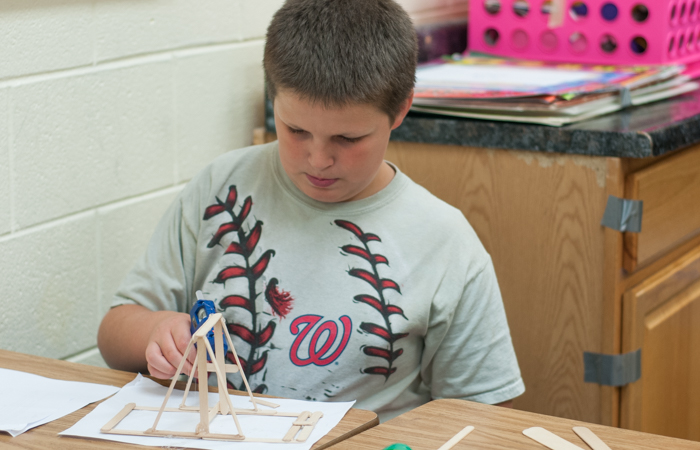 A student using hot glue to create a mini wooden catapult.