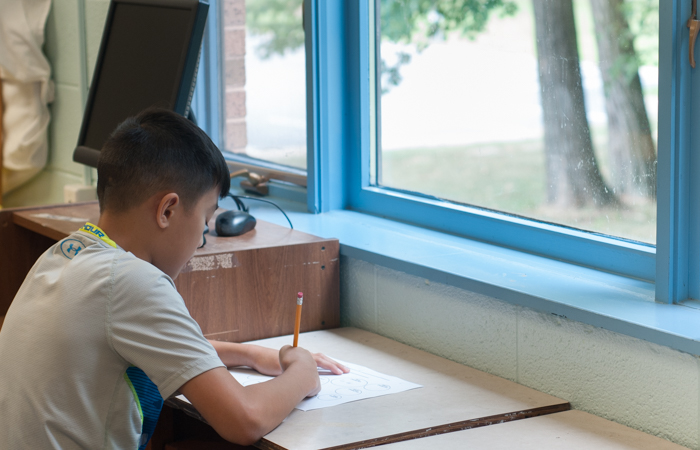 Seated by the window for inspiration, a student begins his first draft.