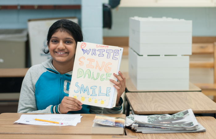 An enthusiastic young writer poses with her folder.