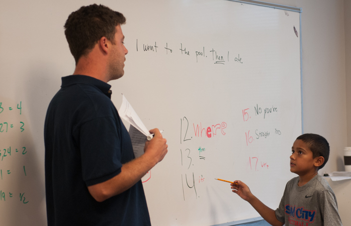 Instructor PJ helps a student with spelling and grammar.