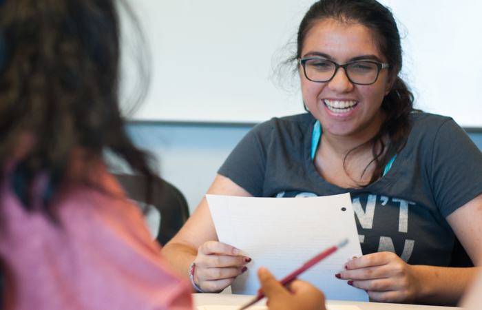 A student laughs as she reads her work to the class.