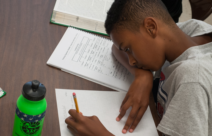 A student works on writing his reading analysis.