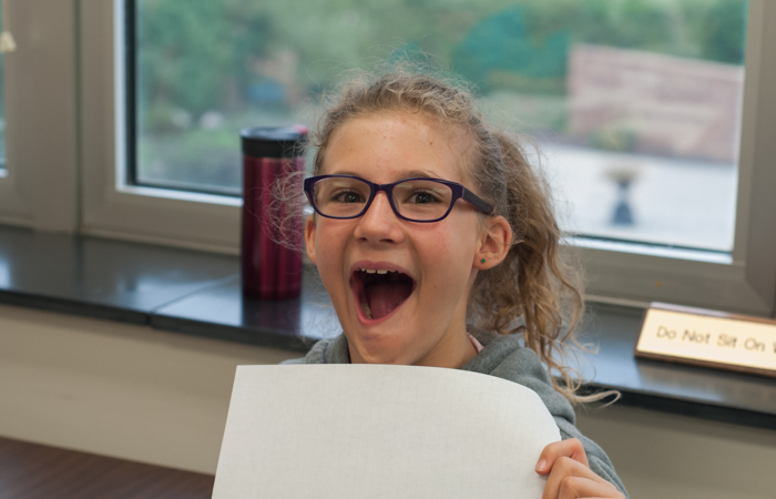 A student gets excited to share her work.
