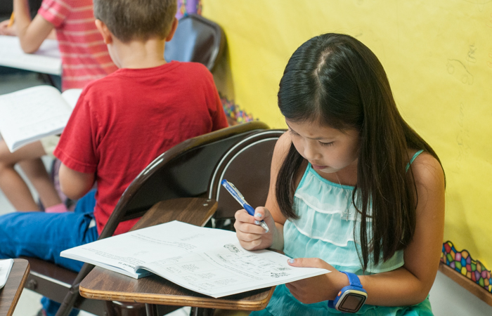 A student uses her workbook to practice mathematics.