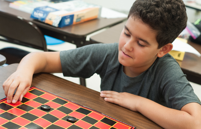 A student carefully makes his next move in a game of checkers.