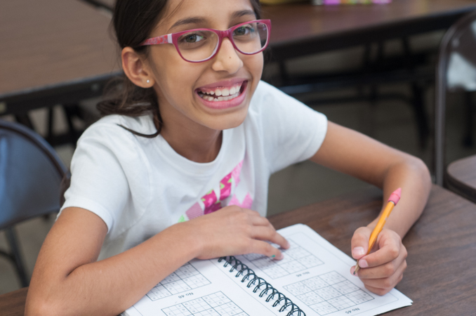 In between Sudoku puzzles, a student smiles for the camera.