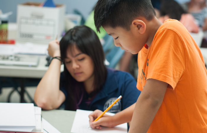 A student completes a math problem as his instructor looks on.