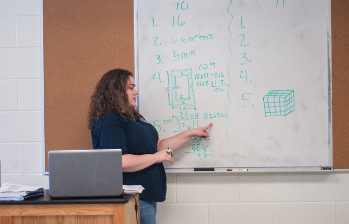 An instructor explains a problem using long division.